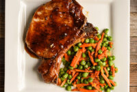 Pork chop glazed in orange-soy sauce, plated with cooked peas and carrots