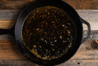 Orange-soy sauce for pork chops, simmering in iron skillet