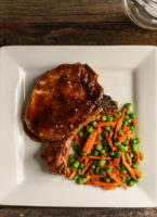 Pork chop in orange-soy sauce, plated with peas and carrots
