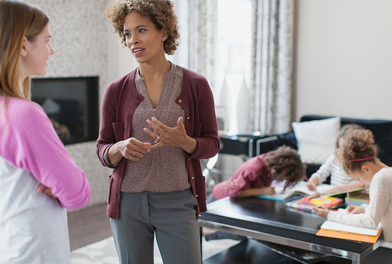 A mom talks with a babysitter while children play in the background.