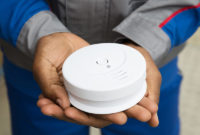 Closeup of a new smoke detector in a man's hands