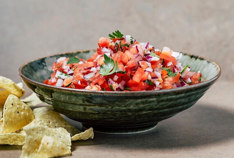 Bowl of tomato-based salsa with chopped cilantro garnish