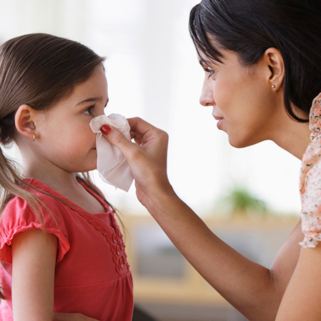 A mother helps her young daughter blow her nose with a tissue.