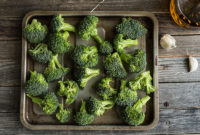 Raw broccoli florets spread on a baking sheet.