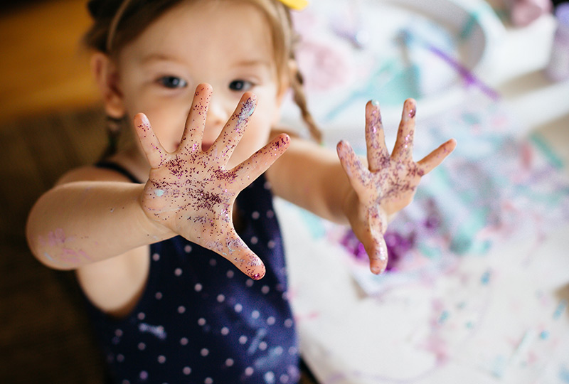 Young girl holds up both hands covered in glitter.