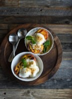 Two bowls with grilled peaches topped with vanilla yogurt.