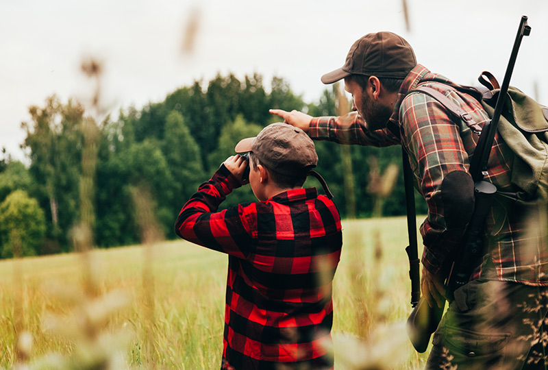 Father and son practicing gun safety while out hunting.
