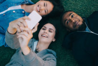 Three teens lying on the grass taking selfies on a cellphone