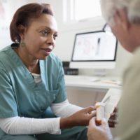 Doctor going over valsartan prescription with patient.