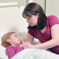 Mother checks on a young girl in bed not feeling well