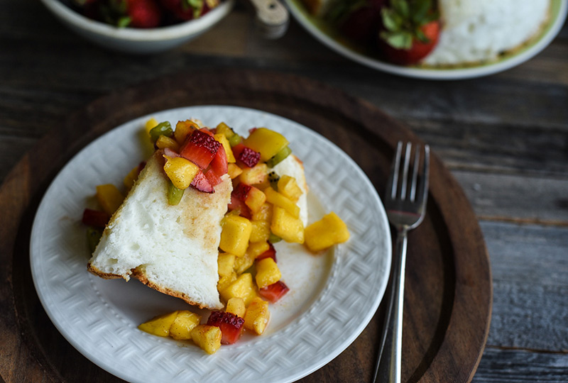 A slice of angel food cake with fruit salsa spooned over it.