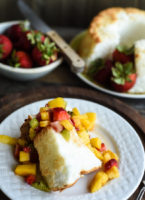 Angel food cake slice with fruit salsa spooned over it.