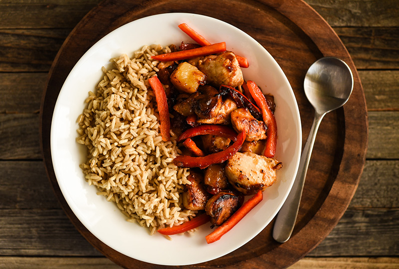 Stir fried chicken, vegetables and pineapple in a bowl with brown rice