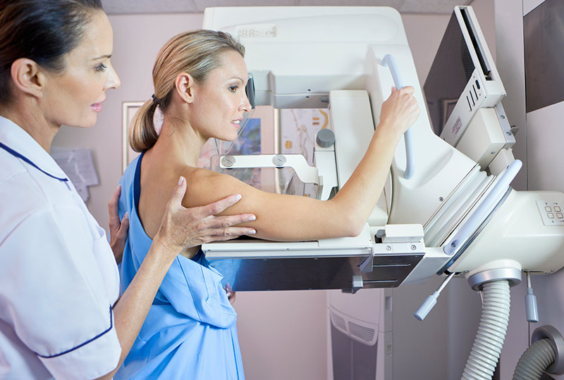 An imaging technician prepares a young woman for a mammogram