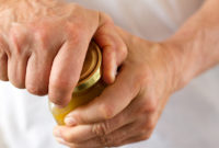 Closeup of a white man's hands as he works to open a jar