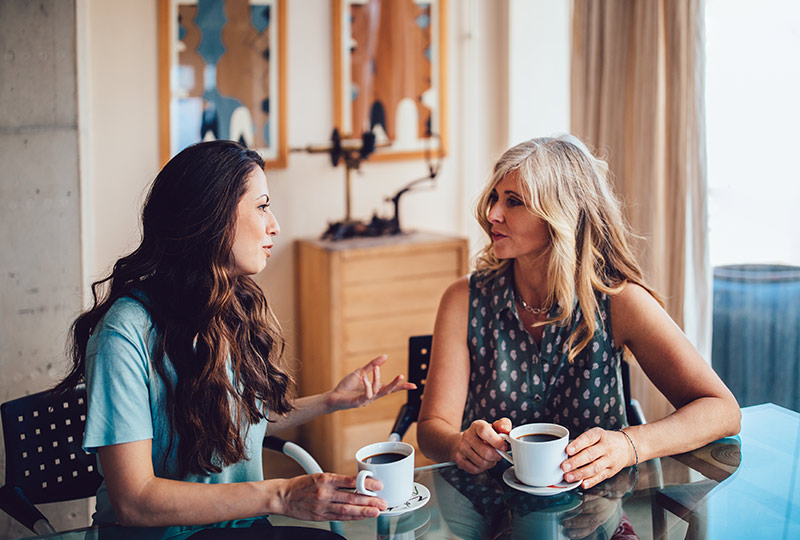 Two women talk while sitting together at a kitchen table drinking coffee