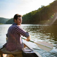Man paddles a canoe on a lake