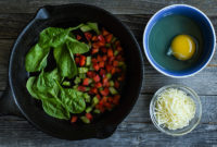 Spinach leaves and chopped peppers in a skillet.