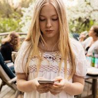 Teen girl looking at phone screen at family gathering.