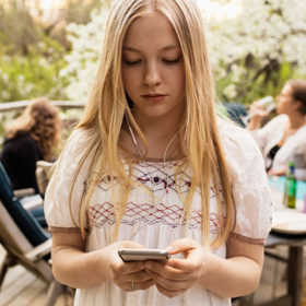 Teen girl looking at phone screen at family gathering.