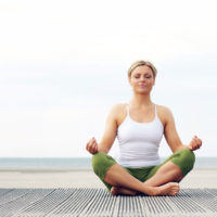 Woman sitting crosslegged in a yoga pose