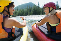 Two women sit in kayaks on a river
