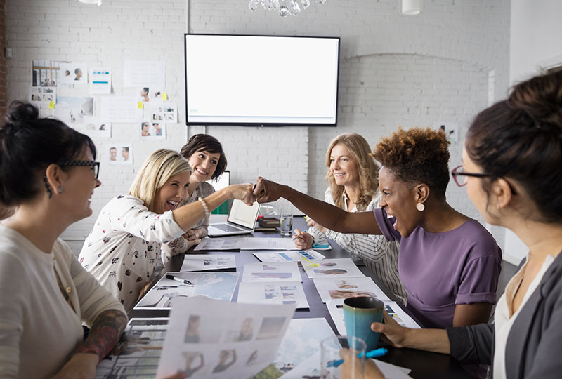 Two women out of a group of women working around a conference table bump fists