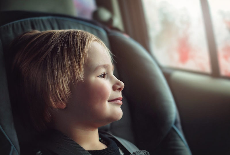 Young boy buckled into car seat gazes out the car window.