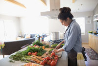 A woman chops a variety of vegetables in a kitchen