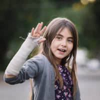 Elementary school girl waving with broken arm wrapped in cast