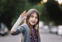 Girl with right arm in a cast waves at the camera