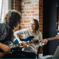 Woman strums a guitar while facing a man also playing guitar