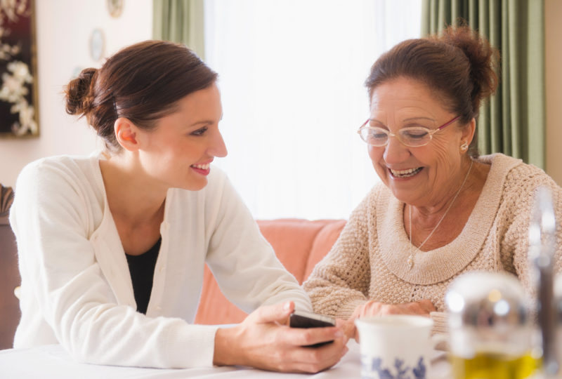 Young woman sits at a table at home with older woman