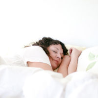 Woman asleep in a bed with puffy white comforter