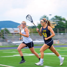 Two teenaged girls playing lacrosse on an outdoor field wearing eye protection.