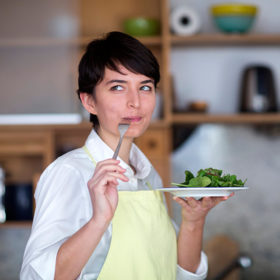 Woman eating a healthy plate of salad greens with sarcastic expression on her face.