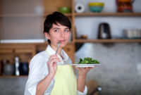Woman eating a plate of salad greens with sarcastic expression on her face.