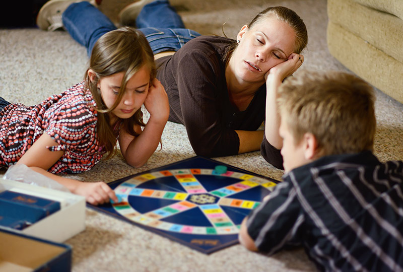 A mom falls asleep playing a board game with two children.
