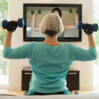 Women lifting weights and watching fitness video at home.