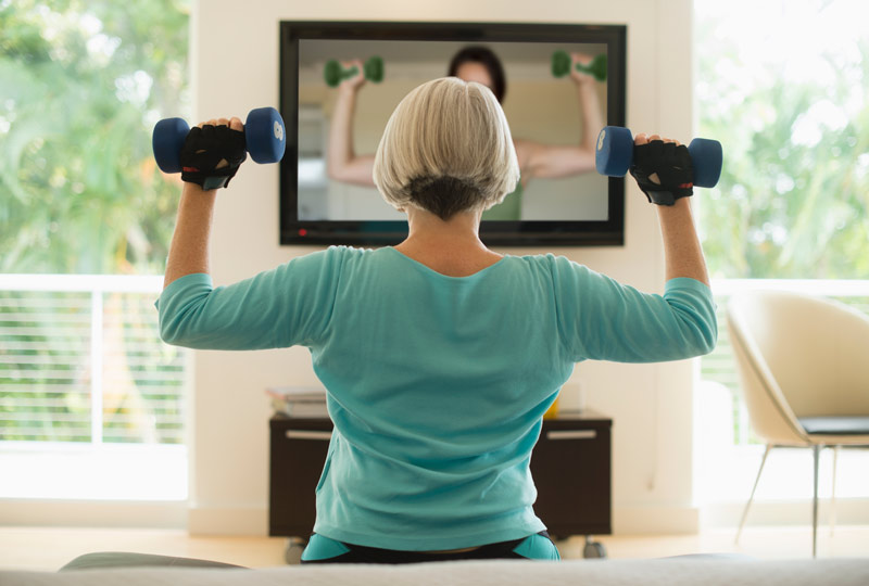 View of older woman from back as she lifts dumbbells while watching an exercise video
