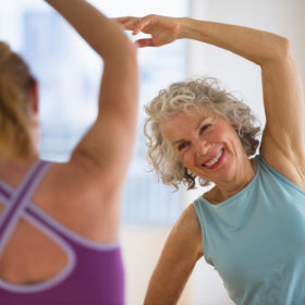 Older woman follows a younger routine by a younger instructor in stretching exercise.