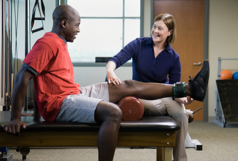Female physical therapist helps man with therapy for his leg.