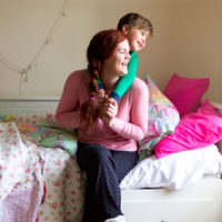 Mother playing with young son in pink bedroom
