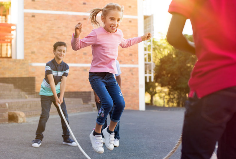 Children staying active and playing jumprope in playground