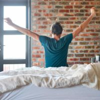 Adult rising from bed and stretching to prevent back pain