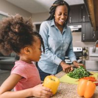 Mother and daughter cooking healthy meal and encouraging healthy living