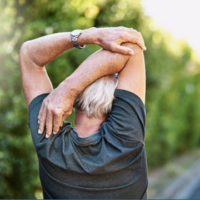 Older man, seen from behind, stretching his triceps.