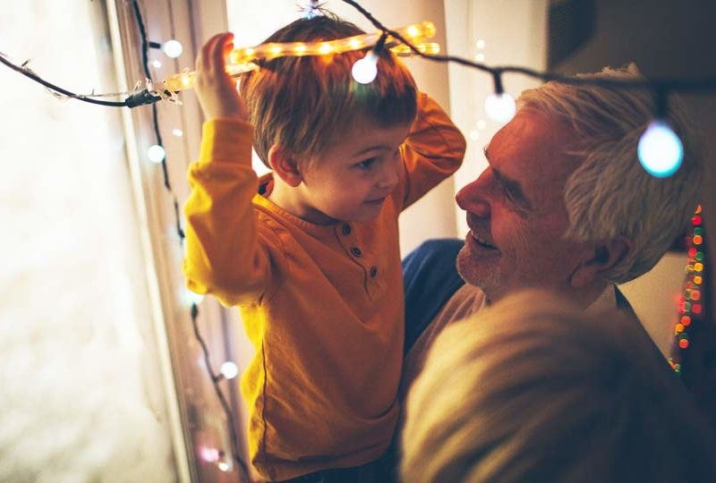 Grandpa spending time decorating for holidays with grandson