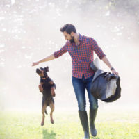 Healthy man walks in a field carrying a saddle, with a dog leaping next to him.