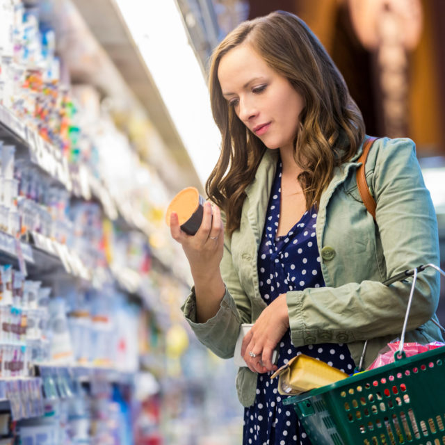 Woman in grocery store reading nutrition facts label.